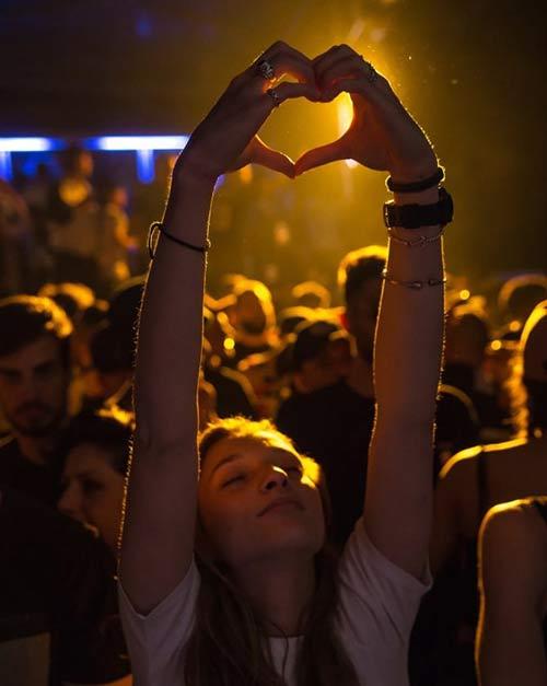 mulher fazendo sinal de coração com as mãos em um evento organizado usando o sistema de gestão de eventos da timely