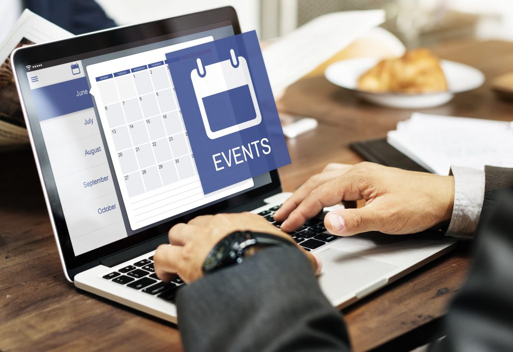 someone's hands working on a laptop, an event calendar is on the screen